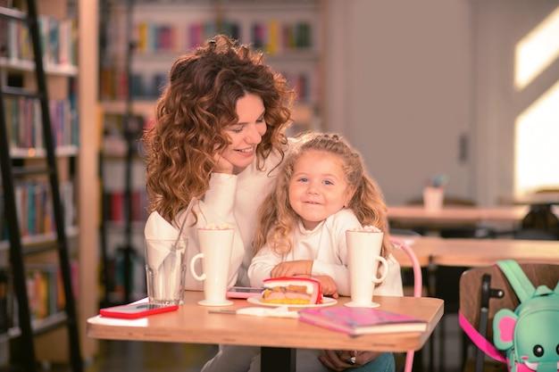 幸せな子供時代。彼女の娘を見つめている間彼女の顔に笑顔を保つ驚くべき巻き毛の髪の女性