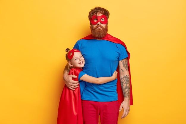 幸せな子供時代と父性の概念。笑顔の小さな赤毛の女性の子供は愛の父と抱きしめます