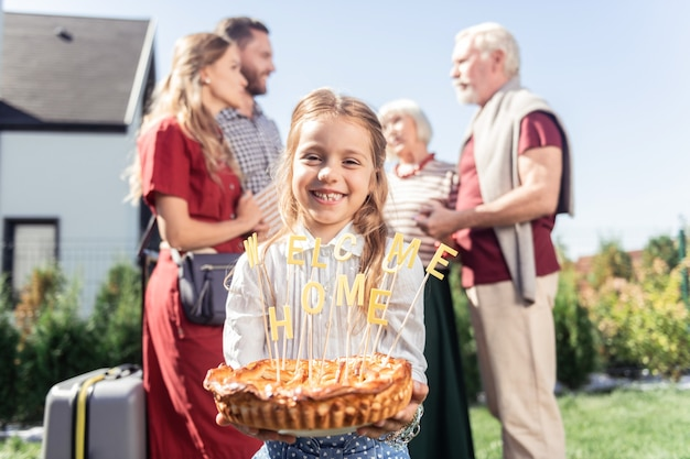 행복한 어린 시절. 축제 케이크를 들고 그녀의 얼굴에 미소를 유지하는 아름다운 여학생