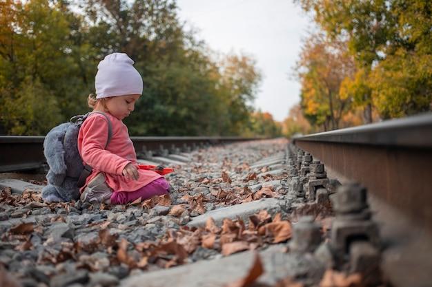 행복한 어린 시절. 아이는 버려진 철도 트랙에서 재생합니다.