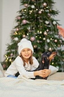 Счастливое детство, волшебная рождественская сказка. маленькая девочка смеется со своим другом, собакой таксой, возле елки.
