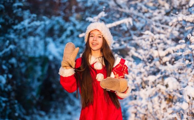 행복한 어린 시절 개념입니다. 행복과 기쁨. 아이 산타 모자. 산타의 선물. 서리가 내린 크리스마스 아침. 기적을 위한 시간. 관대 한 산타 클로스. 눈 덮인 자연 야외에서 아이 행복 한 소녀. 메리 크리스마스.