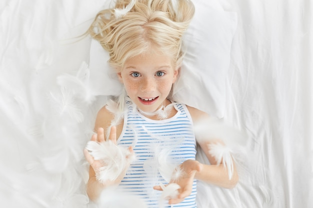 Happy childhood concept. leisure, fun and relaxation. top picture of adorable blonde freckled little girl preschooler looking through flying feathers after pillow fighting in her room