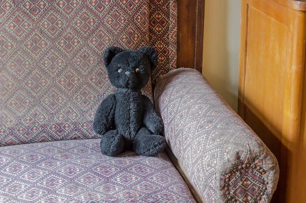 Концепция счастливого детства: ретро игрушки, черный медведь на старом диване