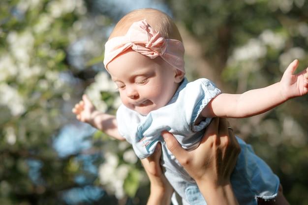 행복 한 어린 시절 즐거운 어머니는 공중에 어린 소녀를 던지고 그의 딸을 던지고