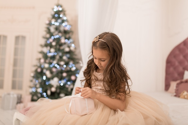 Happy childhood, magical christmas tale. little princess with santa's present for christmas.