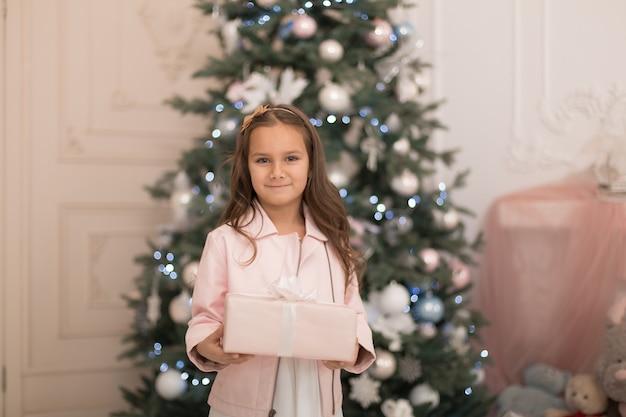 幸せな子供時代、魔法のクリスマスの物語。クリスマスにサンタさんのプレゼントを持ったリトルプリンセス。