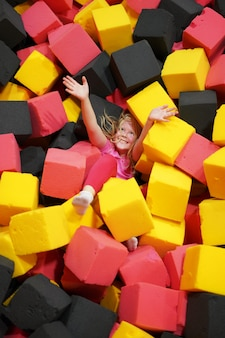 Happy childhood of a modern child in the city - the girl lies in soft cubes in an amusement park