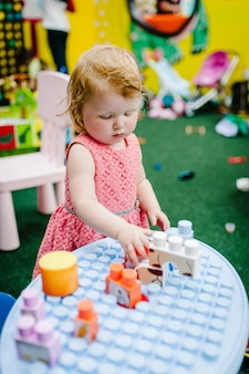 Счастливые дети, маленькая девочка в свой день рождения играет в развивающие игрушки в детской игровой комнате. детский сад. медицинское училище. вечеринка в детском парке развлечений и в игровом центре в помещении.