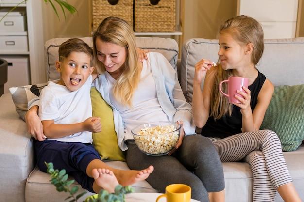 Счастливые дети и ее мать едят попкорн