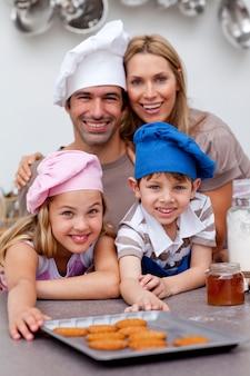幸せな子供たちと両親がビスケットを食べる