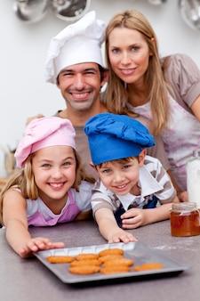 幸せな子供たちと両親は、ベーキング後にクッキー