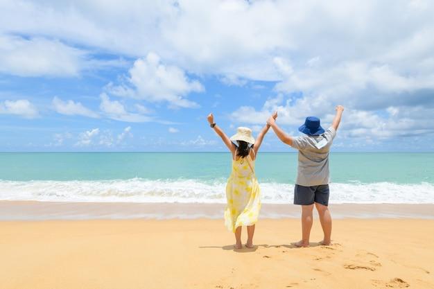 행복한 아이들이 태국 푸켓의 해변에서 함께 손을 들고 돌아왔습니다. 바다 해안에서 휴가를 즐기는 두 매력적인 아이.
