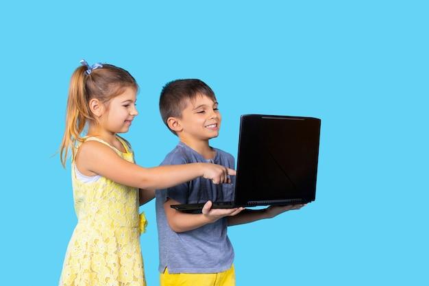 幸せな子供たちは笑顔でノートパソコンの青い孤立した背景娯楽技術の子供たちに座っています