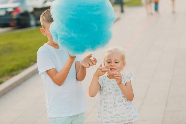 幸せな子供たちの男の子と女の子が屋外で青い綿菓子を食べています。