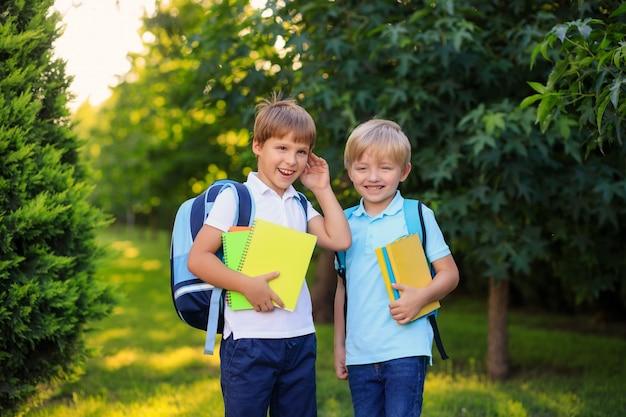 バックパックと本を持つ幸せな子供男の子は学校に戻ります。