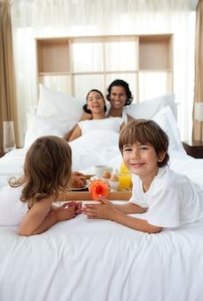幸せな子供たちが朝食を親に持ち帰る