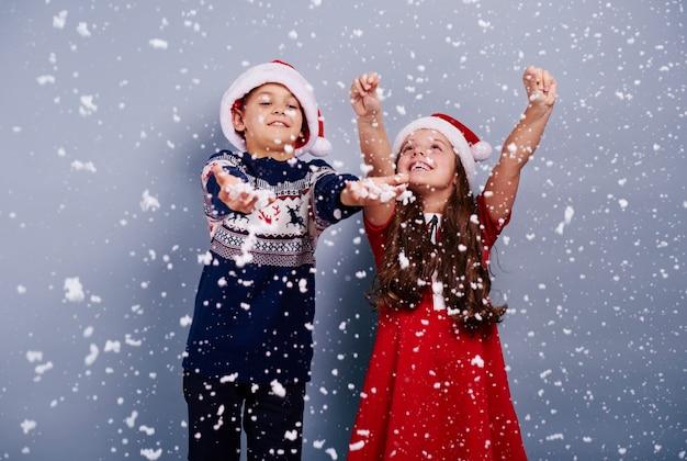 Счастливые дети ловят снежинку