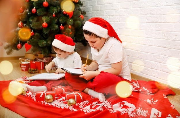 Счастливые дети празднуют рождество в помещении веселые маленькие мальчики