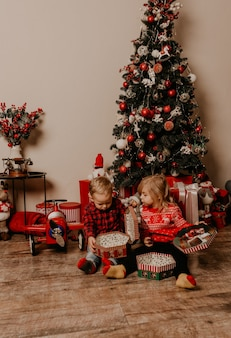 飾られたクリスマスツリーと花輪で新年とクリスマスを祝う幸せな子供たち