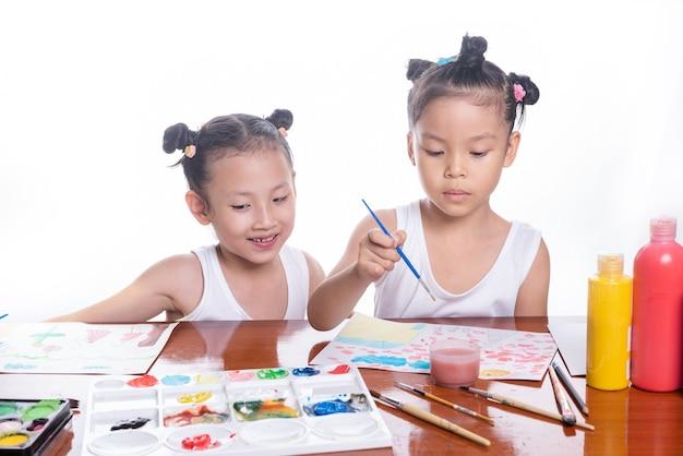 갈색 나무 테이블에 두 명의 작은 아시아 여자의 행복 한 아이들 창조적 인 드로잉 물 컬러 사진. 교육 아이 사람들이 예술 개념.