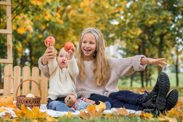 Happy children eating red apple while walking in autumn park.