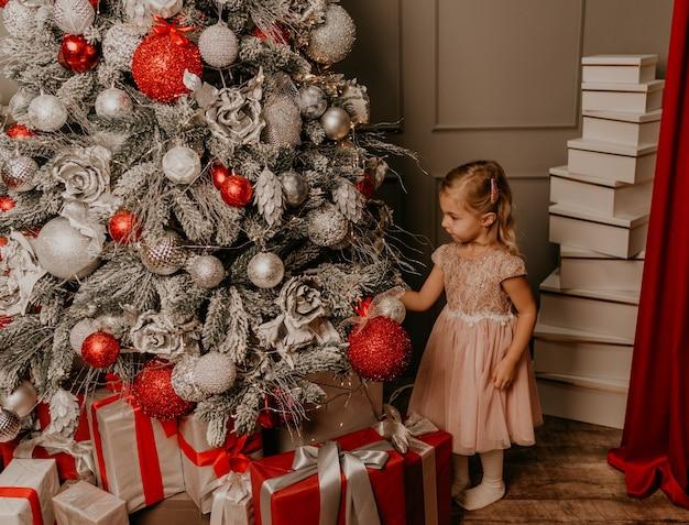 飾られたクリスマスツリーと花輪で新年とクリスマスを祝う幸せな子供たちの女の子