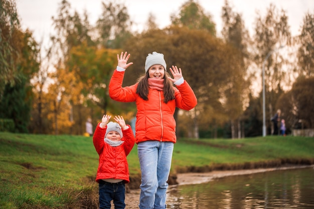 Happy children girls with paper boat in a puddle in autumn on nature outdoors