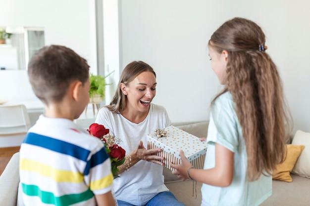 お母さんに花をプレゼントする幸せな子供たち。母の日おめでとう!子供たちの男の子と女の子は笑顔の母親を祝福し、休日のお祝いの間に彼女の花にバラの花束とギフトボックスを与えます