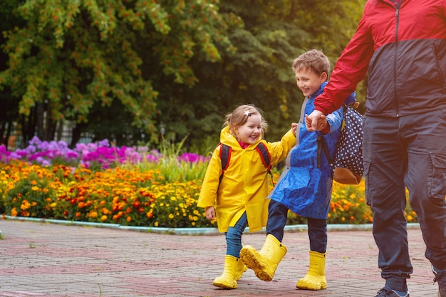 Happy children go to school dressed in raincoats