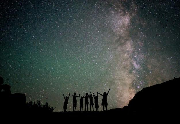 幸せな子どもたちは、銀河系のシルエットと美しい星空の星空を背景に
