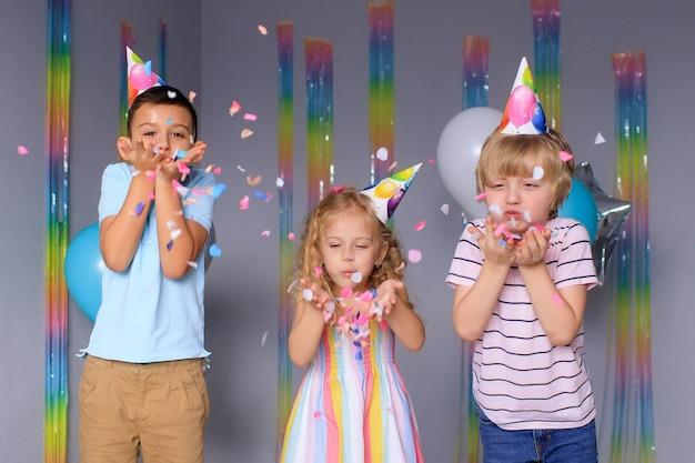 행복한 아이들은 휴일 동안 재미를 즐기고 화려한 색종이를 뛰어 넘습니다.