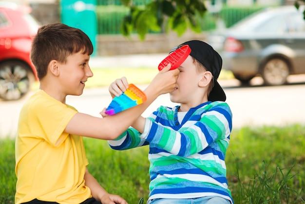 屋外で楽しんで幸せな子供たち。トレンディなポップイットおもちゃで遊ぶかわいい男の子。シリコンの泡のおもちゃで散歩中の友達。子供のための現代の抗ストレス玩具。子供時代、ゲーム、子供向けのレジャー。