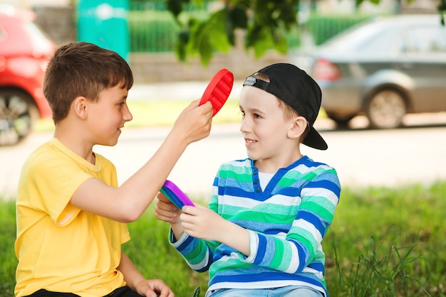 屋外で楽しんで幸せな子供たち。トレンディなポップイットおもちゃで遊ぶかわいい男の子。シリコンの泡のおもちゃで散歩中の友達。子供のための現代の抗ストレス玩具