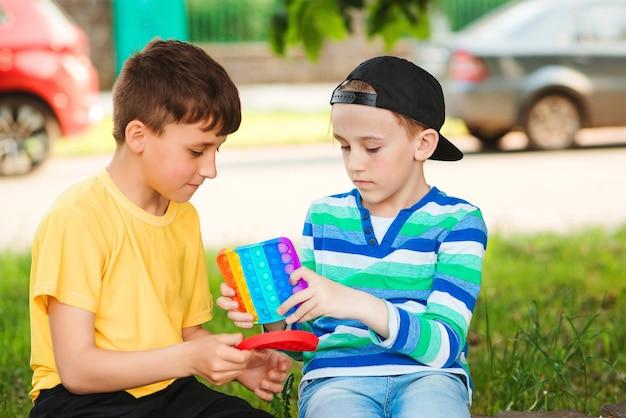 屋外で楽しんで幸せな子供たち。トレンディなポップイットおもちゃで遊ぶかわいい男の子。と散歩中の友達