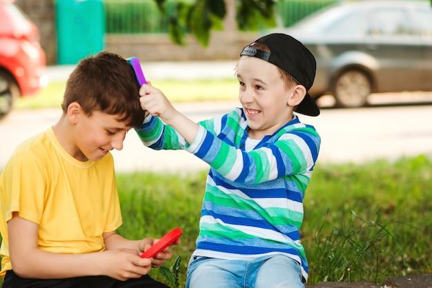 屋外で楽しんで幸せな子供たち。トレンディなポップイットおもちゃで遊ぶかわいい男の子。