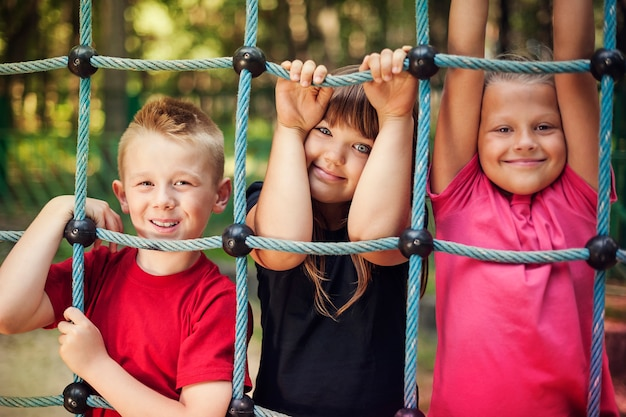遊び場でネットを持っている幸せな子供たち