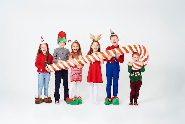 Bambini felici che tengono enorme bastoncino di zucchero