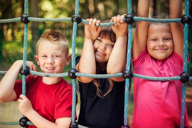 Bambini felici che tengono una rete sul campo da giuoco