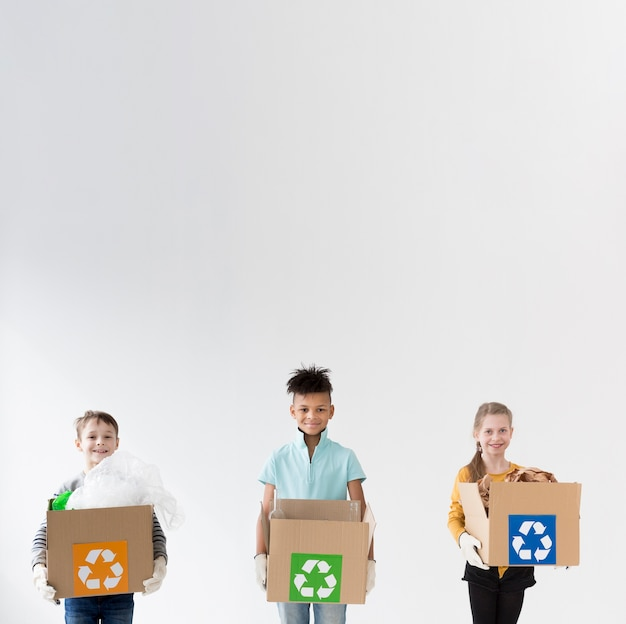 Happy children holding recycling boxes