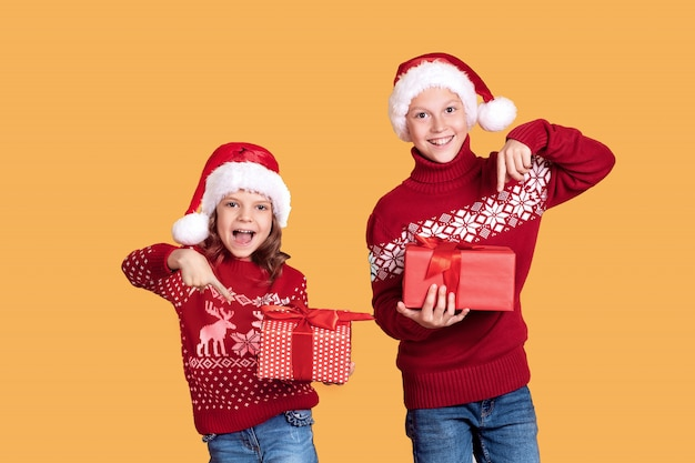 Happy children holding red gift boxes