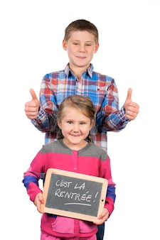Happy children holding a slate on white space