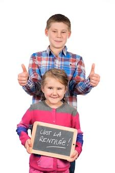 Bambini felici che tengono una lavagna su uno spazio bianco