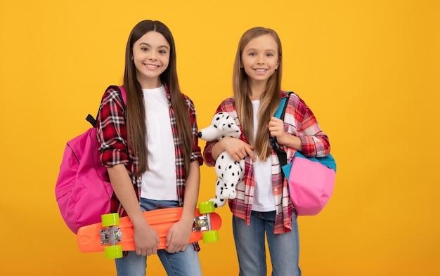 캐주얼한 체크무늬 셔츠를 입은 행복한 아이들은 배낭 장난감과 페니 보드, 힙스터를 가지고 있습니다.