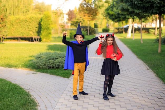 Счастливые дети в парке в костюмах на хэллоуин отмечают праздник