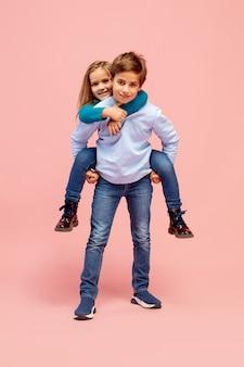 Bambini felici isolati su sfondo rosa corallo studio. sembra felice, allegro, sincero. copyspace. infanzia, educazione, concetto di emozioni