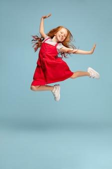 Счастливые дети, изолированные на синем фоне студии. выглядит счастливым, жизнерадостным, искренним. copyspace. детство, образование, концепция эмоций