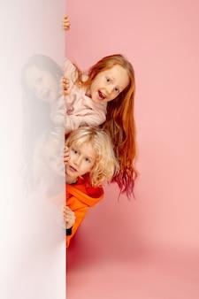 コーラルピンクのスタジオの背景に分離された幸せな子供たち。幸せ、陽気、誠実に見えます。コピースペース。幼児期、教育、感情の概念