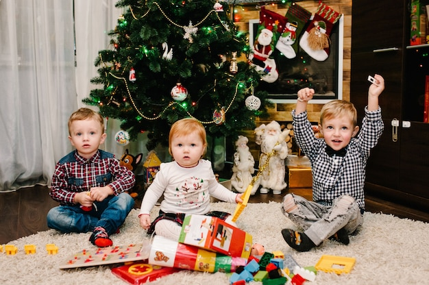 Happy children, kids, daughter and son, boy and girl unpack gifts near christmas tree and fireplace.