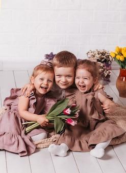 Счастливые дети смеются и обнимаются в комнате с цветами. брат и две сестры